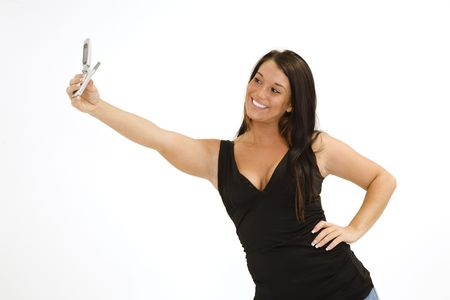 A beautiful young female caucasian wearing an casual outfit and using a cell phone to take a picture of herself.   She is on a white background.  photo