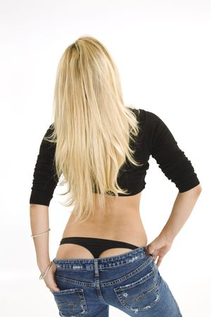 A beautiful caucasian woman standing with her back to the camera and wearing a black thong. She is standing on a white background Stock Photo