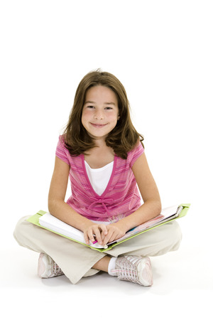 Child sitting on a white background with school books and smiling