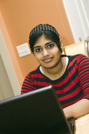 conputer: Portrait of Indian teenager working with a laptop conputer Stock Photo