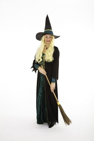 ghoulish: Caucasian woman dressed as a scary witch standing on white background