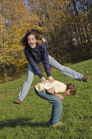 horsing around: Caucasian teens one male and one female horsing around in a park playing leapfrog Stock Photo