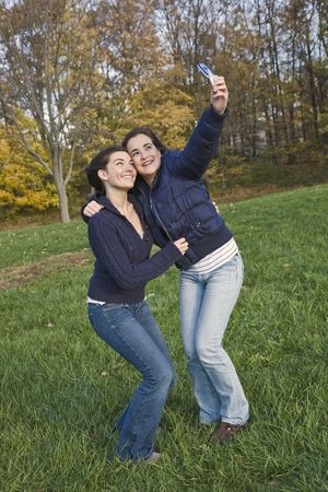horsing around: Two caucasian teenage females horsing around in a park using a cell phone to take their pictures