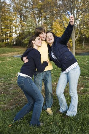 horsing around: Three caucasian teens one male and two females horsing around in a park using a cell phone to take their pictures