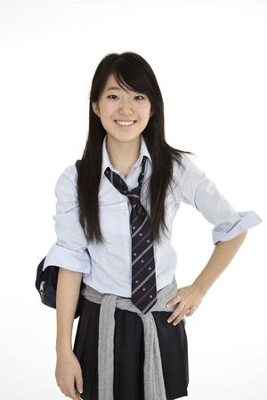 uniform student: Portrait of a female Asian teenager dressed in the traditional Japanese schoolgirl clothing.  Uniforms are worn by most of the female school children in Japan.  She is standing on a white background and smiling.