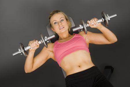 early 20s: Cauc�sicos mujer en poco m�s de 20 a�os el levantamiento de pesas utilizando una pesa sobre un fondo gris