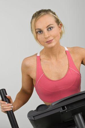 early 20s: Caucasian mujer en poco m�s de 20 a�os en el ejercicio de una m�quina cardiovascular