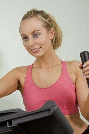 cardiovascular exercising: Caucasian woman in early 20s exercising on a cardiovascular machine