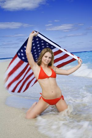Beautiful Caucasian female teenage kneeling on the beach and holding an United States Flag while wearing a red bikini.