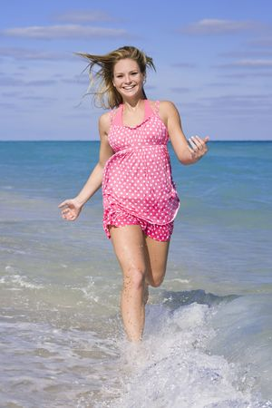 Beautiful Caucasian female teenage running through to surf wearing a colorful sundress.  Stock Photo