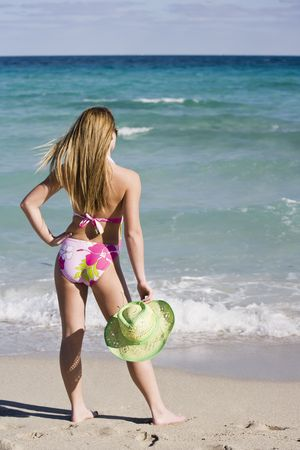 Beautiful Caucasian female teenage standing in the surf wearing a colorful one piece swimsuit.