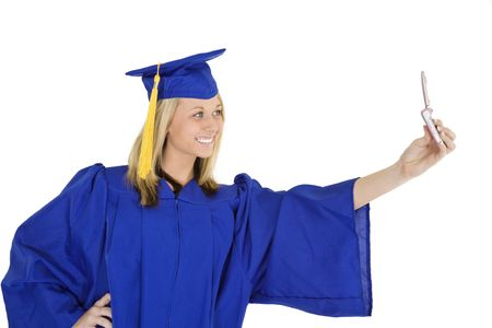 An Caucasian teenage in blue graduation gown and smiling while holding a  cell phone and taking a picture of herself.  She is on a white background.  photo
