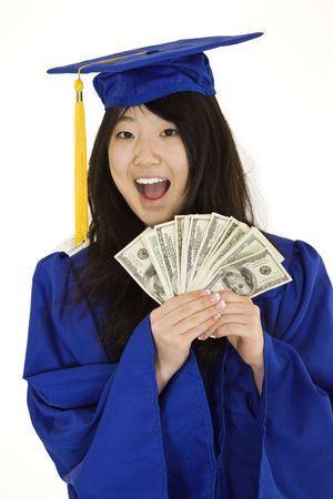 exuberant: An Asian teenage in blue graduation gown and smiling while hold US money to illustrate to high cost of education.  She is on a white background.