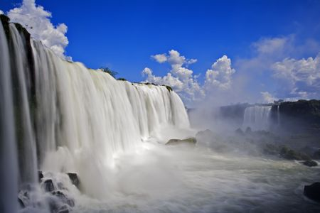 Iguassu Falls is the largest series of waterfalls on the planet, located in Brazil, Argentina, and Paraguay.  At some times during the year one can see as many as 275 separate waterfalls cascading along the edges of 2,700 meters (1.6 miles) cliffs. Argent Stock Photo