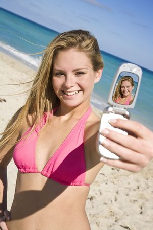 bathingsuits: Beautiful Caucasian female teenage standing on the beach and using a cell phone to take a picture of herself.  She is wearing a colorful pink bikini.  Stock Photo