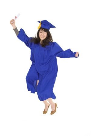 exuberance: An Asian teenage in blue graduation gown and smiling and jumping in joy.   She is on a white background.  Stock Photo