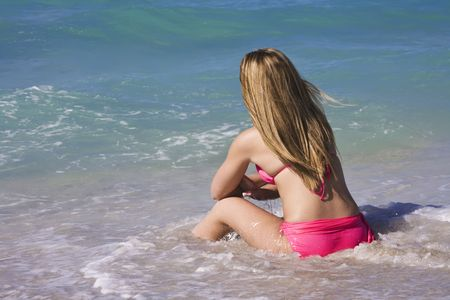 bathingsuits: Beautiful Caucasian female teenage sitting in the surf wearing a colorful pinkrbikini.