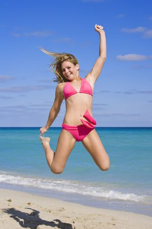 flesh colour: Beautiful Caucasian female teenage having fun on South Beach jumping into the air wearing a swimsuit Stock Photo