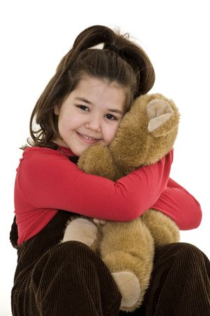 Caucasian child hugging a teddy bear with a big smile on her face.