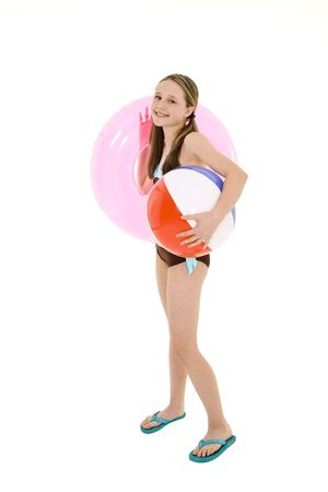 youngsters: Preteen caucasian girl standing on a white background in a swimsuit holding a beach toy and smiling Stock Photo