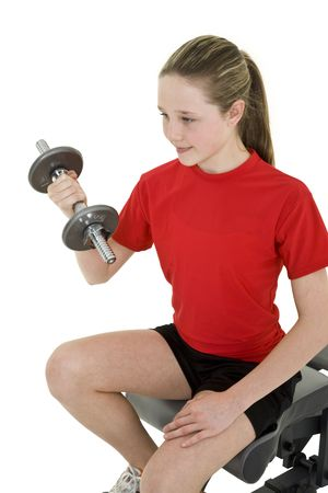 whitebackground: Caucasian preteen female lifting weights using a dumbbell on a white background