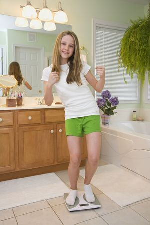 weighting: Caucasian preteen very excited about her weight