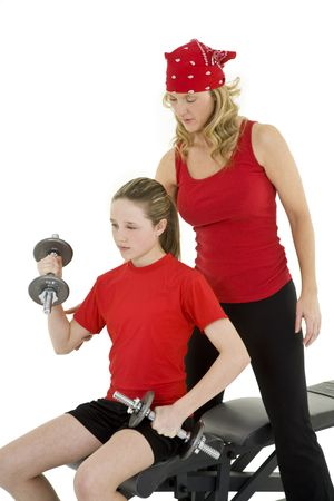 Caucasian mother helping her preteen daughter to lift weights using a dumbbell on a white background photo
