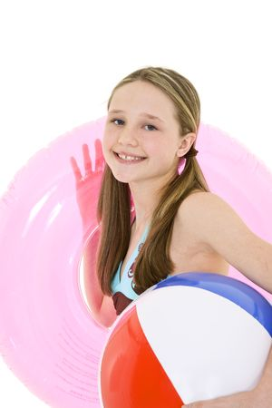 Preteen caucasian girl standing on a white background in a swimsuit holding beach toys and smiling photo