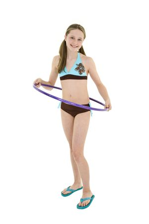 beautiful preteen girl: Preteen caucasian girl standing on a white background in a swimsuit holding a hula hoop