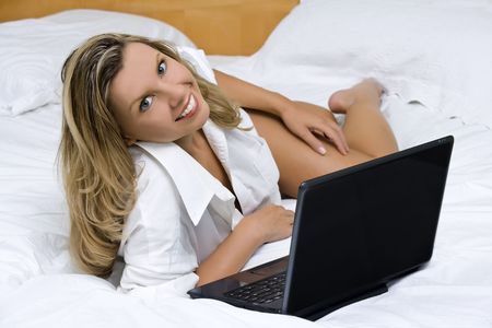 Beautiful caucasian woman laying in bed working on a laptop computer photo