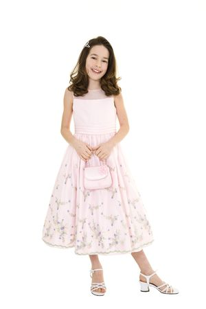 Young caucasian girl dressed in a Easter dress and standing on a white background.