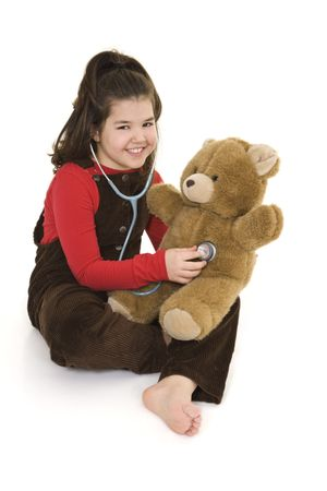 Caucasian child using a stethoscope to pretend she is listening to her teddybears  heart beat photo