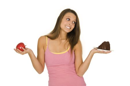 Caucasian woman holding an apple and slice of chocolate cake trying to decide which one to eat Stock Photo - 3280625