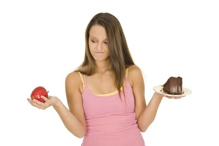 Caucasian woman holding an apple and slice of chocolate cake trying to decide which one to eat Stock Photo - 3315310