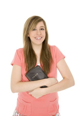 Beautiful caucasian teenager holding a bible on a white background