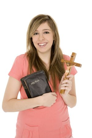 Beautiful caucasian teenager holding a bible and crucifix on a white background photo