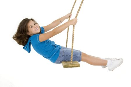 Caucasian child playing on a swing on white background