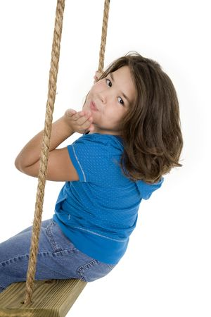 Caucasian child playing on a swing on white background photo