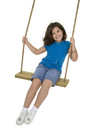 Caucasian child playing on a swing on white