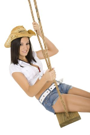 Caucasian cowgirl in wooden swing on white background photo