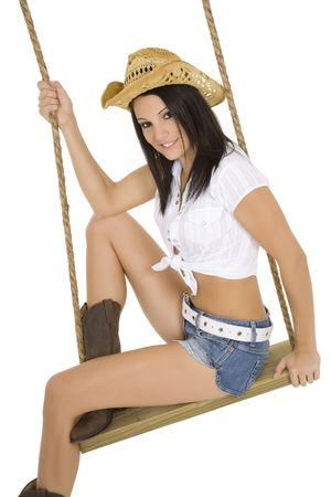 Caucasian cowgirl in wooden swing on white  photo