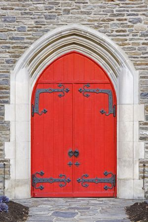 Red church doors on a old stone church