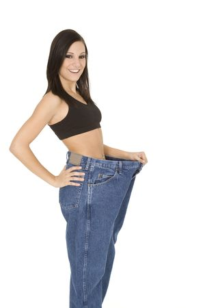 Caucasian woman hold old jeans to show weight loss Stock Photo