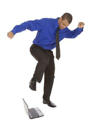 African American businessman kicking a computer on white background photo