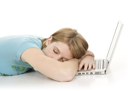 tried: Caucasian teenager sleeping while working on a laptop computer Stock Photo