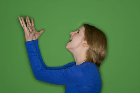 expressing: Beautiful Caucasian teenager who is very angry on green background
