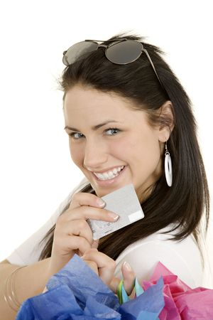 Excited Caucasian woman holding shopping bags and a credit card smiling on white background photo