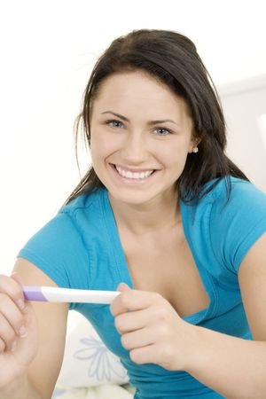 fertilize: Young Caucasian woman holding a pregnancy test Stock Photo