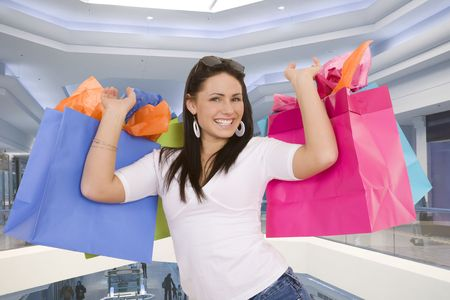 copysapce: Excited Caucasian woman holding shopping bags and smiling in a shopping mall