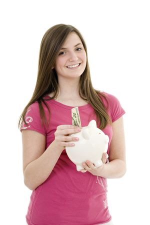 Caucasian teenager holding a piggy bank on white background photo